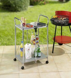 Chromservierwagen mit Essen und Trinken auf den Ablageflächen sowie ein roter Grill im Hintergrund
