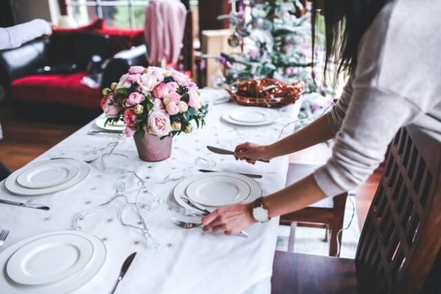 Kellnerin deckt einen Tisch richtig ein