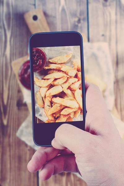 Frau fotografiert ihr Essen für Instagram